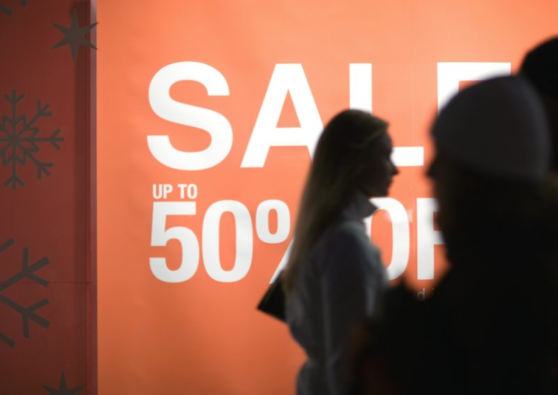 Poster proclaiming Sale up to 50% off and shoppers silhouetted in foreground