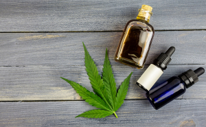 Hemp leaf on wooden background, cannabis oil extracts in bottles
