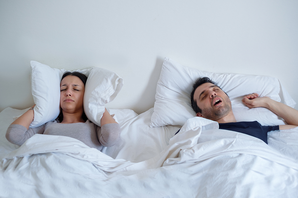 Woman suffering insomnia and man snoring in bed