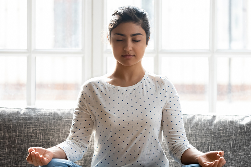 Calm woman with closed eyes meditating at home alone close up,