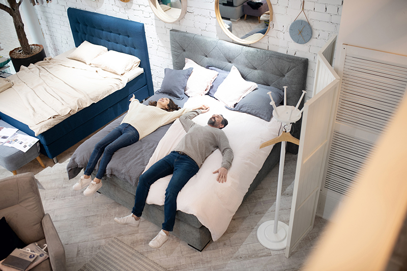 Moderm bedroom. Man and woman laying on bed furniture salon