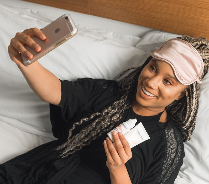 sleep box subscription - girl in bed taking selfie with sleep products