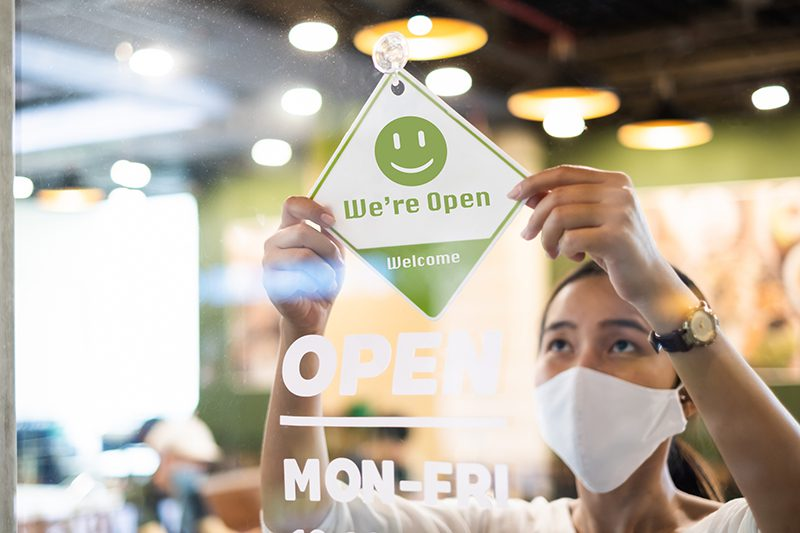 Business owner woman wear protective face mask ppe hanging open open again after lock down due to outbreak of coronavirus covid-19
