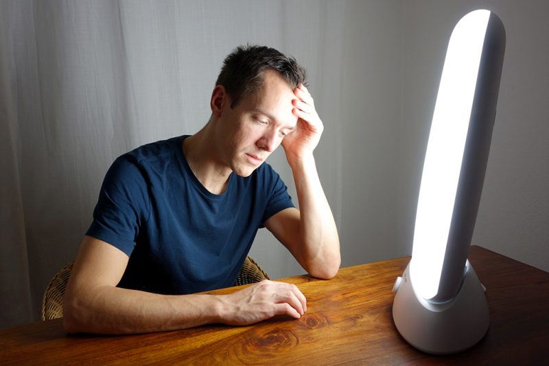 Man sitting in front of a light therapy lamp, a common treatment for seasonal affective disorder