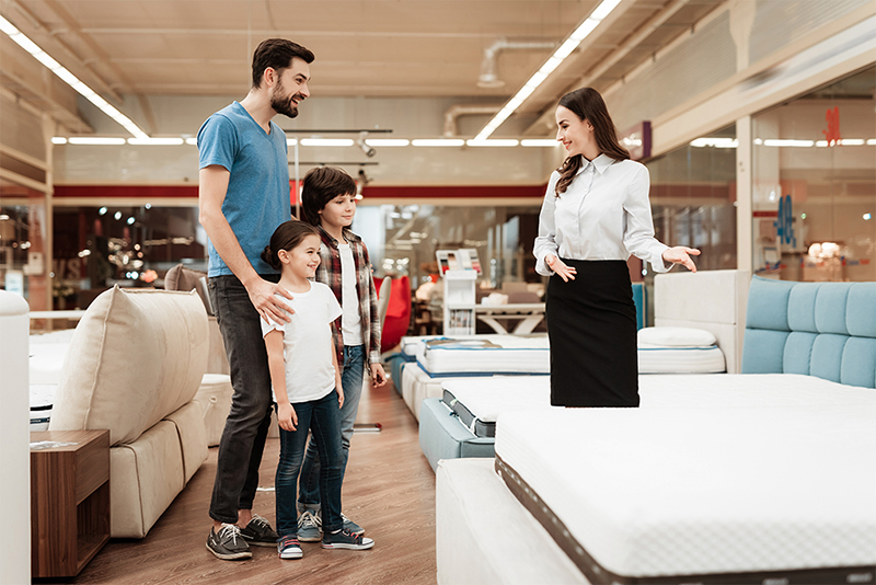 Family Mattress Shopping - man and two kids talking to woman next to mattress