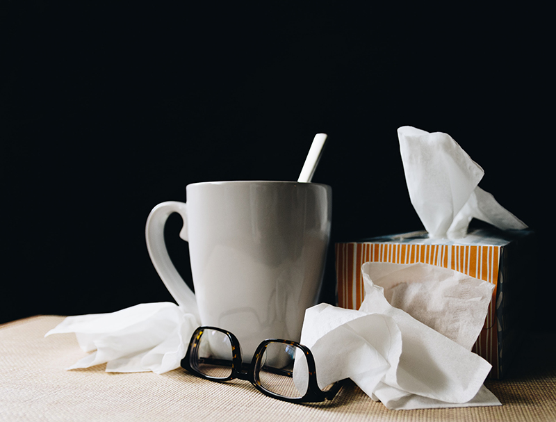 allergies and sleep - a white mug next to a pair of glasses and a box of tissues