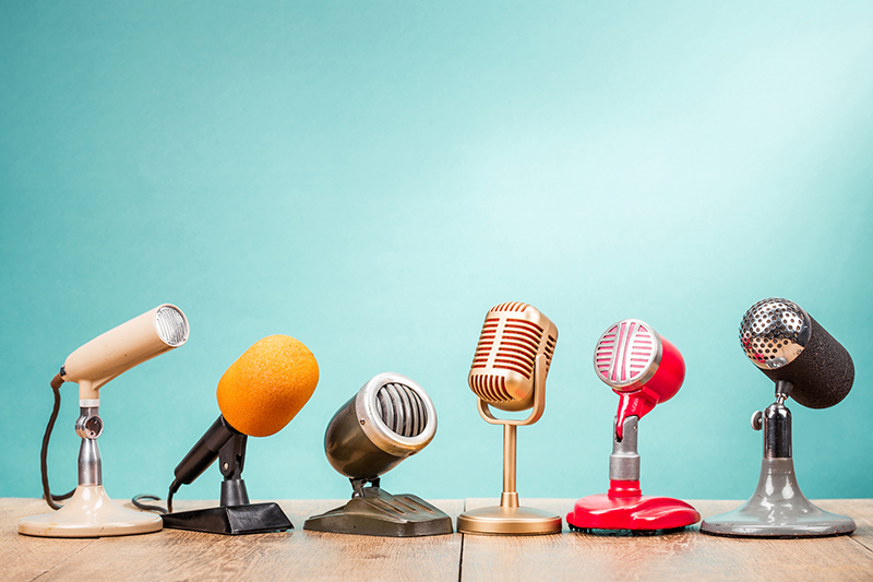 Retro old microphones on table front gradient aquamarine background. Vintage old style filtered photo