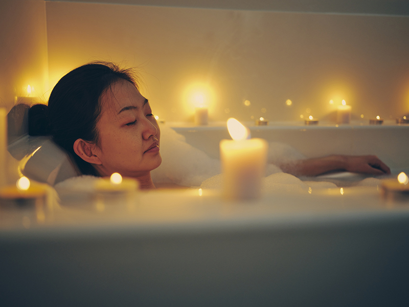 A young Asian woman relaxing in a bathtub, surrounded by candles.