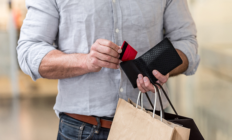 Man taking credit card from his wallet, holding shopping bags.