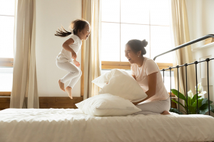 In morning carefree small daughter jump on bed while mother laughing feels happy