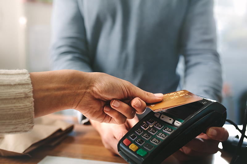 Retailer accepting credit card by contactless payment.