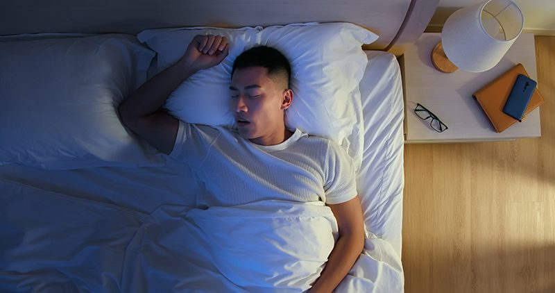 top view of asian young man snores when he sleep at night