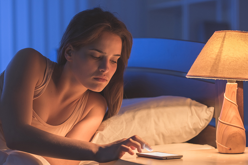 The woman lay on the bed and phone. night time