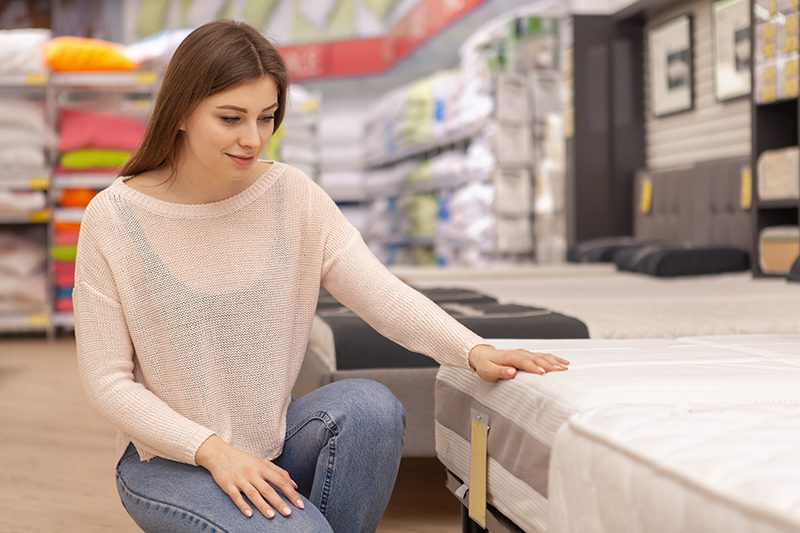 Young woman examining mattress on sale at home furnishings store
