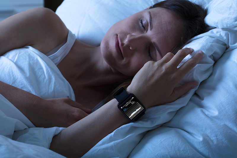 Close-up Of A Woman Sleeping With Smart Watch Showing Heartbeat Rate On Bed
